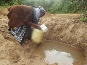 The Water Project : kenya4300-03-a-woman-fetching-water-in-scoophole-at-river-muvui