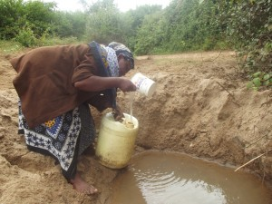 The Water Project : kenya4300-05-a-woman-fetching-water-in-scoophole-at-river-muvui