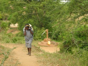 The Water Project : kenya4301-14-second-member-carries-water-home