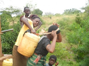 The Water Project : kenya4301-34-members-carry-water-home
