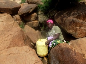 The Water Project : kenya4307-kee-woman-fetching-water-from-a-rock-02