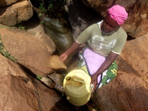 The Water Project : kenya4307-kee-woman-fetching-water-from-a-rock-03