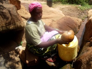 The Water Project : kenya4307-kee-woman-fetching-water-from-a-rock-12