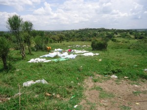 The Water Project : uganda6054-11-laying-washed-clothes-on-grass-now-decreasing