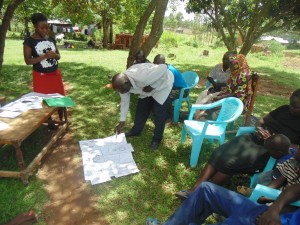 The Water Project : kenya4264-17-market-members-demonstrating-the-disease-transmission-routes