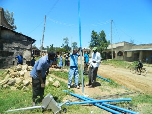 The Water Project : kenya4264-31-fixing-the-cylinder-to-the-pipes