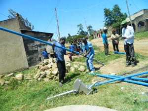 The Water Project : kenya4264-33-fixing-the-cylinder-to-the-pipe