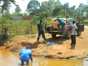 The Water Project : kenya4333-32-fetching-water-from-a-river-2km-away-to-be-used-for-drilling