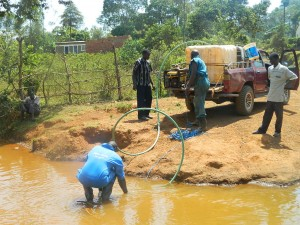 The Water Project : kenya4333-34-fetching-water-from-a-river-2km-away-to-be-used-for-drilling