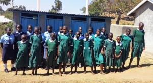 The Water Project : 8-kenya4647-girls-pose-in-front-of-their-only-latrines