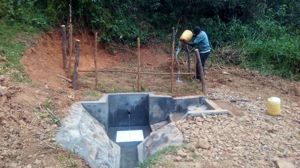 28 kenya4704 community member waters grass at spring