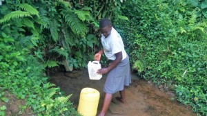The Water Project : 2-kenya4845-lady-fetching-water-at-musila-spring